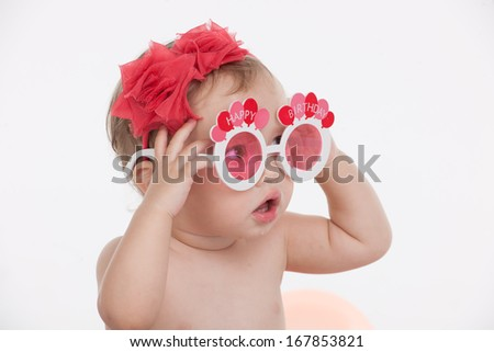 Portrait of Funny little baby girl in funny party glasses. Sitting and looking away with surprise isolated over white background  - stock photo