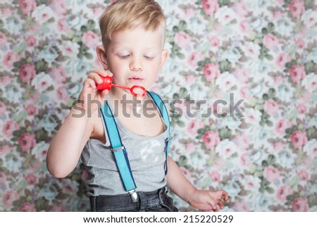 Portrait of funny little boy blowing soap bubbles. Background: floral, soft, pastel  - stock photo