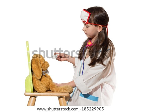 Portrait of funny little caucasian girl in medical costume gives mixture to rabbit toy isolated on white - stock photo