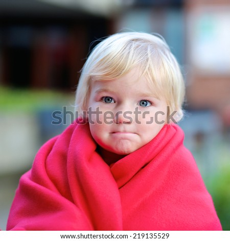 Portrait of funny little child, adorable blonde toddler girl wrapped in warm red plaid outdoors - stock photo
