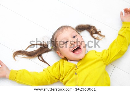 Portrait of funny little girl lying on floor - stock photo