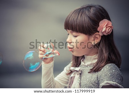 Portrait of funny lovely little girl blowing soap bubble - stock photo