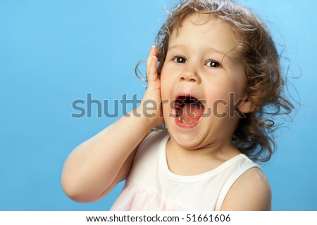 Portrait of funny lovely little girl on the blue background - stock photo