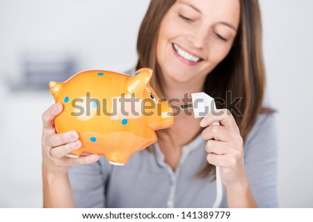 Portrait of funny mid adult woman holding electric plug and piggy bank - stock photo
