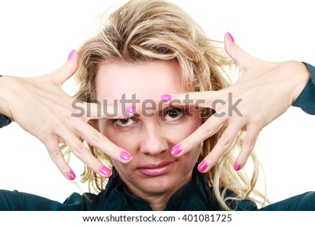 Portrait of funny middle aged blonde woman. Adult female wearing blue blouse showing pink nails in front of face.