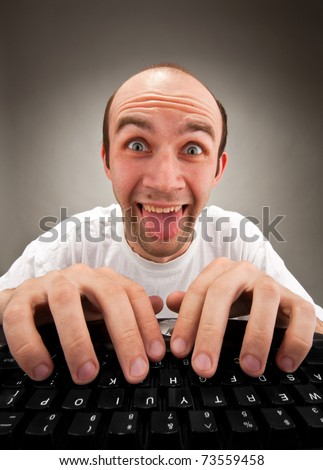 Portrait of funny nerd working on computer