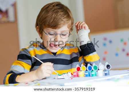 Portrait of funny preschool kid boy with glasses and broken hand drawing. Little child having fun with colorful watercolors and gouache, indoors. School, education concept - stock photo