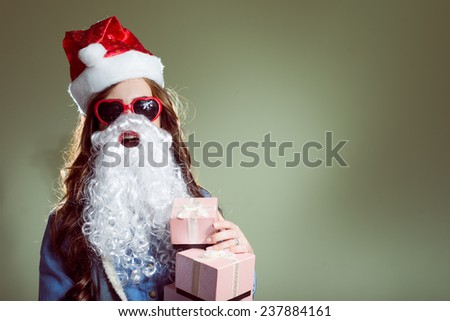 portrait of funny pretty girl in Christmas hat, glasses and beard holding presents looking at camera - stock photo