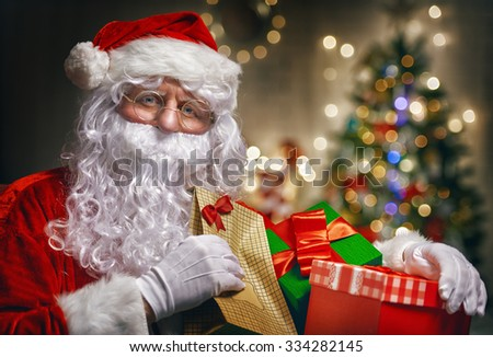 Portrait of funny Santa Claus with christmas gifts - stock photo