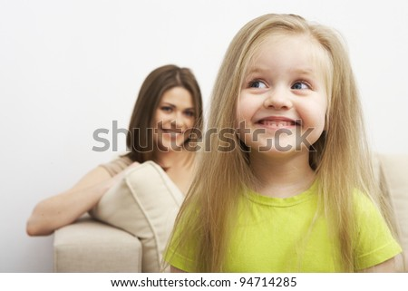 Portrait of funny smiling little girl with mother. Idea child - stock photo