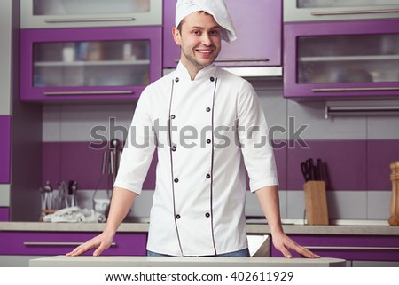 Portrait of funny smiling man in cook uniform posing in modern kitchen. Indoor shot