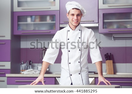 Portrait of funny smiling man in cook uniform posing in modern kitchen. Indoor shot - stock photo