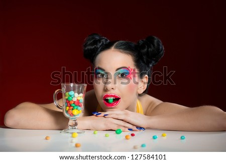 Portrait of funny woman with colorful makeup and candy drops
