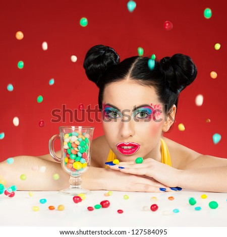 Portrait of funny woman with colorful makeup under the falling candy drops