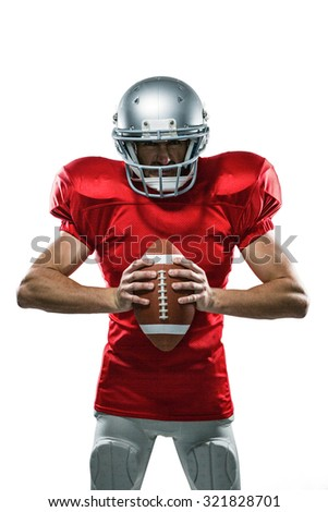 Portrait of furious American football player in red jersey and helmet holding ball on white background - stock photo