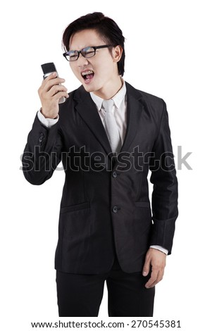 Portrait of furious businessman wearing formal suit and yelling on his cellphone, isolated on white - stock photo