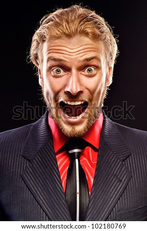 portrait of furious young man shouting on a black background - stock photo