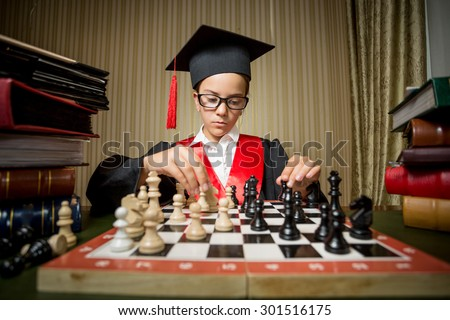 Portrait of genius girl in graduation cap playing chess with herself - stock photo
