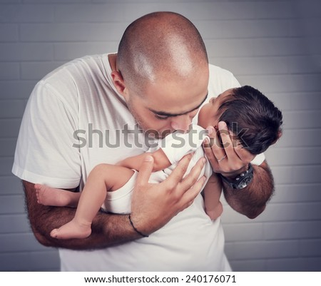 Portrait of gentle father kissing his little newborn daughter, enjoying  at home, happy fatherhood concept - stock photo