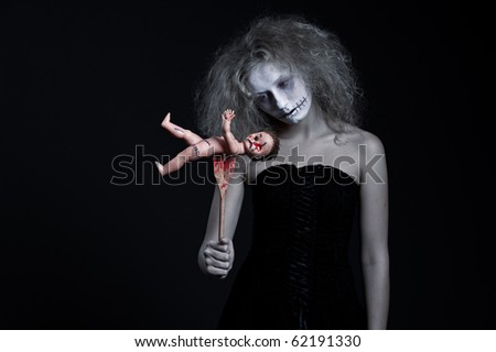 portrait of ghost with bloody doll over black background - stock photo