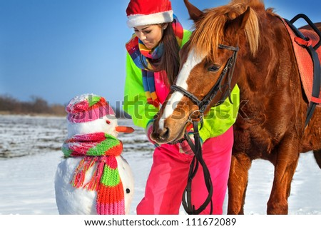 Portrait of girk with horse and snowman in winter landscape.