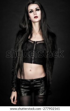 Portrait of girl-alien with black eyes in dark clothes