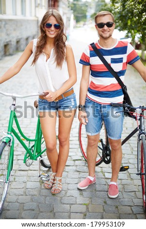 Portrait of girl and guy with bicycles looking at camera in the park - stock photo