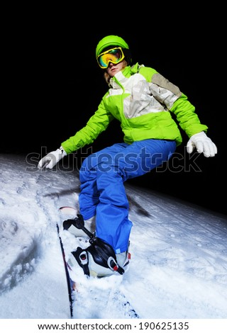 Portrait of girl balancing on snowboard at night - stock photo