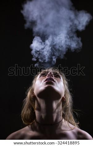 Portrait of girl blowing smoke - stock photo