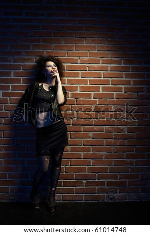 portrait of girl dressed like hooker posing near brick wall - stock photo
