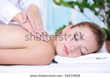 Portrait of girl getting back massage and relaxation in the spa salon - stock photo