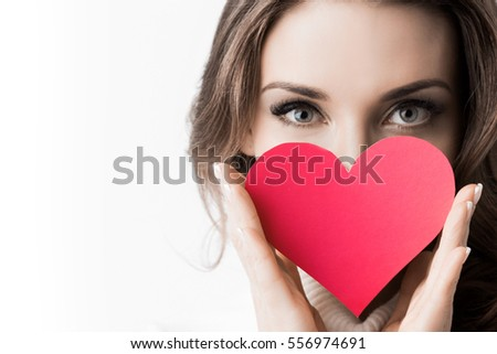 Portrait of girl holding red paper heart isolated on white background