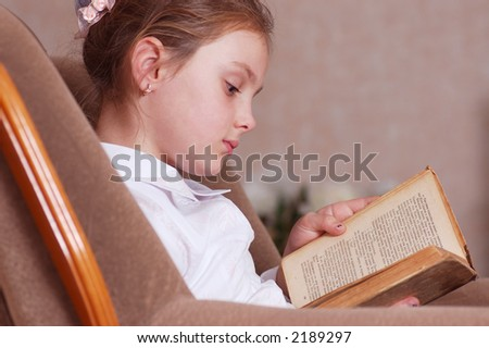 Portrait of girl in an armchair with book in hands
