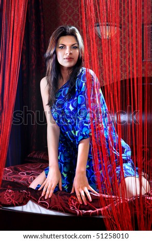portrait of girl in dark blue dress which is in red bedroom - stock photo