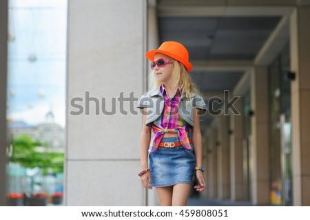 Portrait of girl in fashionable clothes. Elegant Charming cute little girl in sunglasses, orange hat. Adorable happy child walking in big mall along window displays and looking. Shopping in big store. - stock photo