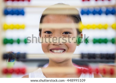 Portrait of girl in front of abacus in classroom