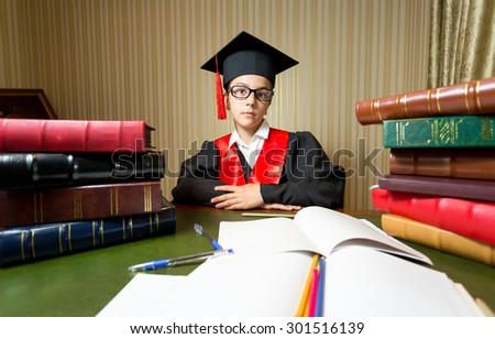 Portrait of girl in graduation cap and black gown sitting at library - stock photo