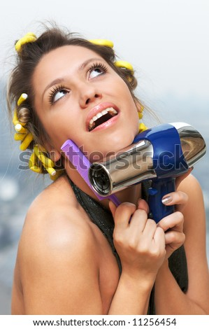 portrait of girl in hair rollers with hair-dryer and comb (shallow DOF)