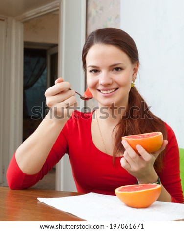 Portrait of girl in red eats grapefruit at home   - stock photo