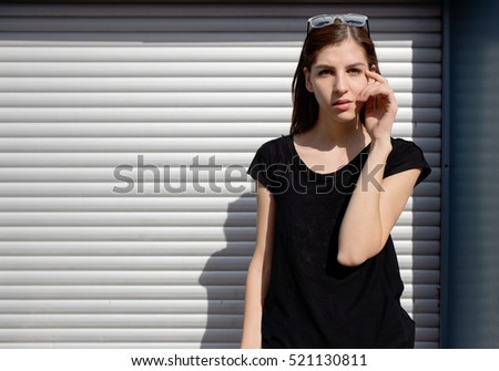Portrait of girl in rock black style, standing outdoors in the city against the silver metal urban wall