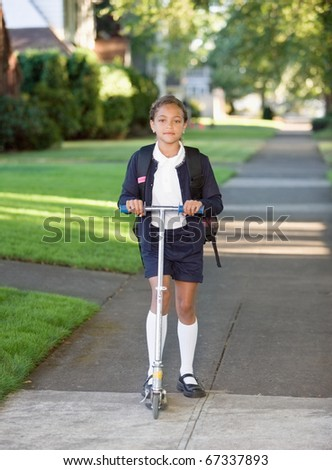 Portrait of girl in school uniform with scooter - stock photo