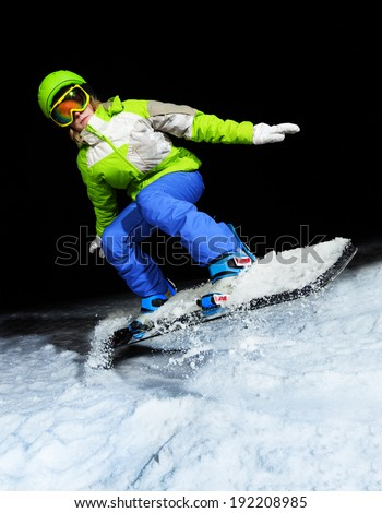 Portrait of girl jumping on snowboard at night - stock photo