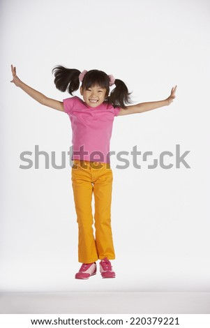 Portrait of girl jumping with arms out - stock photo