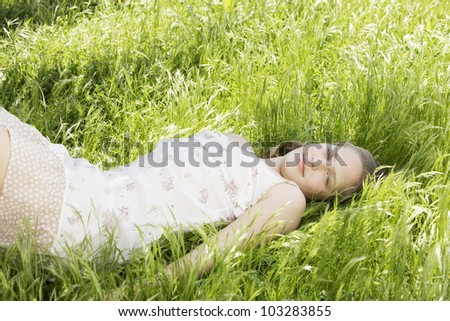 Portrait of girl laying down on long green grass in the garden. - stock photo