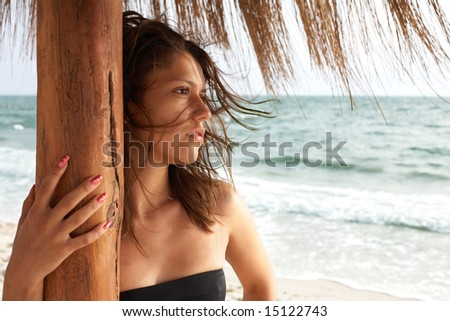 portrait of girl on beach under beach umbrella; sea on background