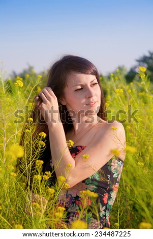 Portrait of girl on nature in yellow flowers