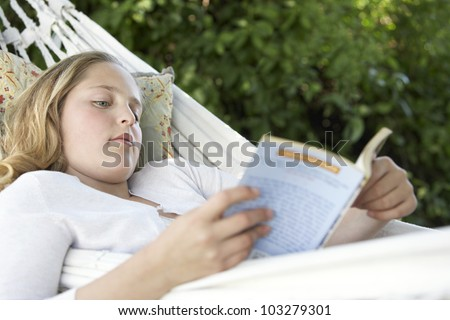 Portrait of girl reading a book while laying down on a hammock in the garden. - stock photo