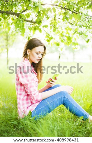 Portrait of girl sit down under blooming flowers on apple tree on fresh green grass in spring garden background hold cell mobile phone in hand, sun shine in blossom, beauty of nature and woman concept