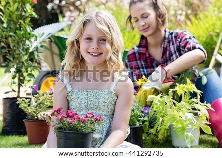 Portrait of girl sitting in garden with flower pot while mother gardening in background - stock photo
