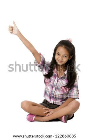 Portrait of girl smiling while making thumb ups gesture against white background